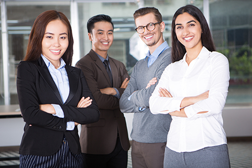 Closeup portrait of four smiling young business people looking at camera and standing with arms crossed and cafe interior in background